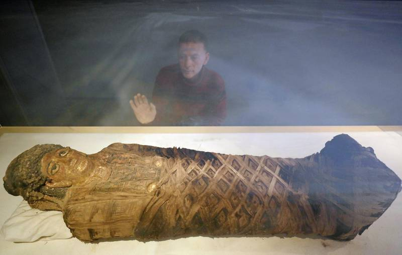 A visitor stands beside a mummy dated back to The Greco-Roman Period, discovered in a cemetery , on display in Bahariya Oases near village of Bawity, Egypt March 20, 2021. REUTERS/Mohamed Abd El Ghany REFILE - CORRECTING LOCATION