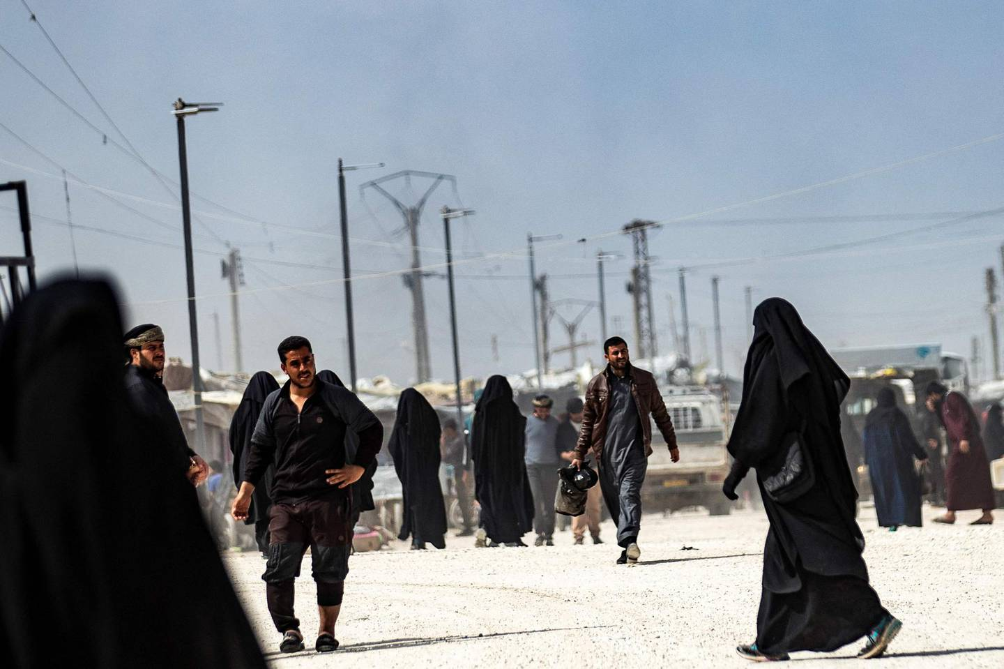 (FILES) In this file photo taken on March 3, 2021, people walk at the Kurdish-run al-Hol camp which holds suspected relatives of Islamic State (IS) group fighters, in Hasakeh governorate of northeastern Syria. Kurdish authorities launched a security sweep in the camp where they arrested dozens today, a war monitor and Kurdish officials said.  / AFP / Delil SOULEIMAN