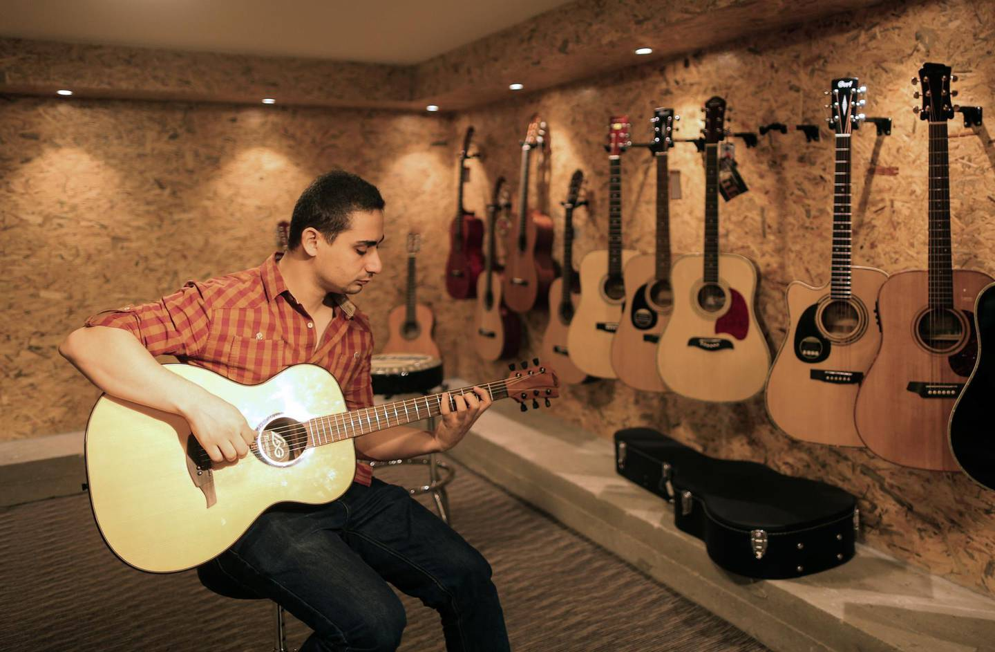 Raji al-Jaru plays a guitar at his music shop in Gaza City on September 27, 2017. - Jaru is the first shop in Gaza, that sells musical instruments. (Photo by MAHMUD HAMS / AFP)