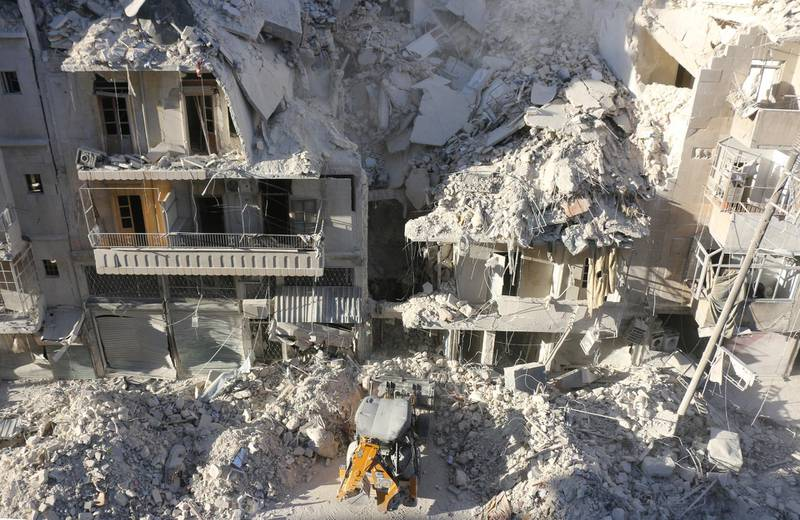 A tractor clears the rubble following Syrian govermnet forces airstrikes in the rebel held neighborhood of Tariq a-Bab in Aleppo on September 24, 2016. - Residents in Syria's battleground city of Aleppo cowered indoors as fierce air strikes toppled buildings and killed at least 52 civilians, after diplomatic efforts to revive a ceasefire failed. (Photo by THAER MOHAMMED / AFP)