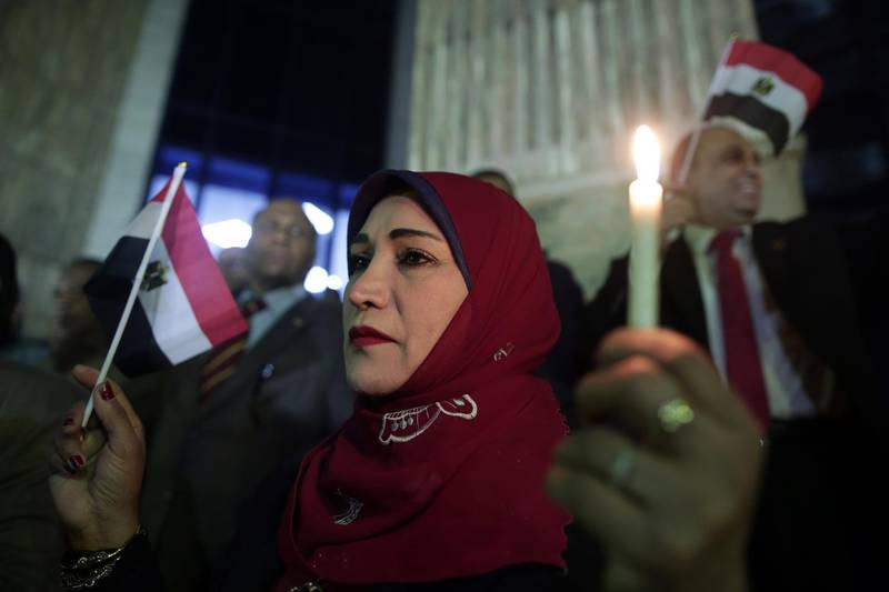 epa06354387 Egyptian Jornalists hold candles and the Egyptian national flag during candlelight vigil for victims of al-Rawda mosque attack, in front of the Journalists Syndicate, in Cairo, Egypt, 27 November 2017. 305 people were killed and 128 injured after a bomb was detonated at a mosque and fire opened on worshippers during Friday prayers in the Sinai town of Bir al-Abd, near Arish (400km northeast of Cairo) on 24 November.  EPA/KHALED ELFIQI