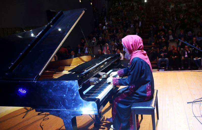 Palestinian pianist Yara Thabit plays the piano during a concert to mark the debut of Gaza's only grand piano after it was rescued from conflict, at a theater nestled in the Palestinian Red Crescent Society's building in Gaza City, Sunday, Nov. 25, 2018. The only grand piano in the Gaza Strip is debuting to the public for the first time in over a decade after its restoration. (AP Photo/Adel Hana)