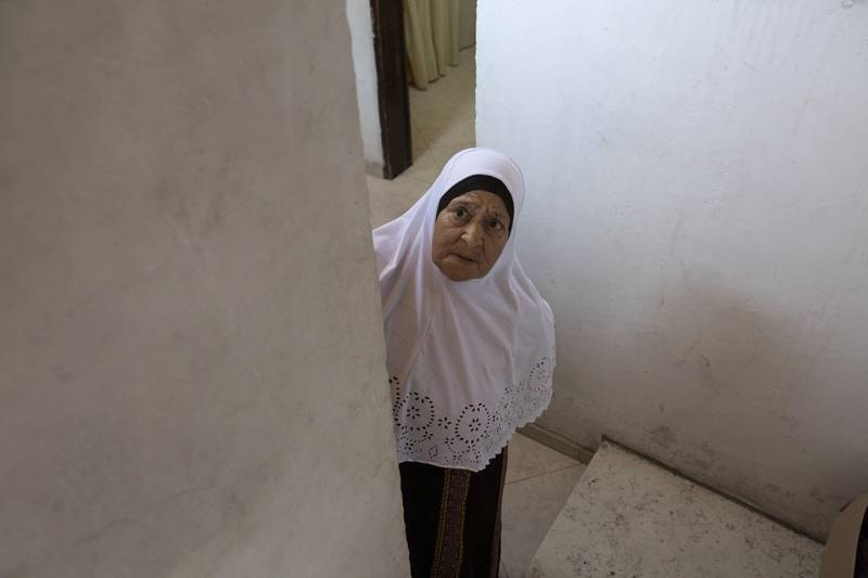 Fatima Shamasneh looks towards the street from the stairs of her her tiny basement  home in the East Jerusalem neighborhood of Sheik Jarrah on August 11,2017.  When thehamasne family first moved into their home  in the 1960s, East Jerusalem was controlled by Jordan and their monthly rent was paid to  Jordanian authorities but since  Israel annexed East Jerusalem in 1967, the Shamasne family has paid their rent to Israel's general custodian in order to remain in the building. The family claims that their payments were suddenly rejected in 2009 , and they were informed that the property had been claimed by Israeli Jews whose ancestors had lived there decades previously.Although the family has spent years fighting to remain in the home , the Israeli high court has ruled that the family must evacuate the home before August 9. (Photo by Heidi Levine for The National).