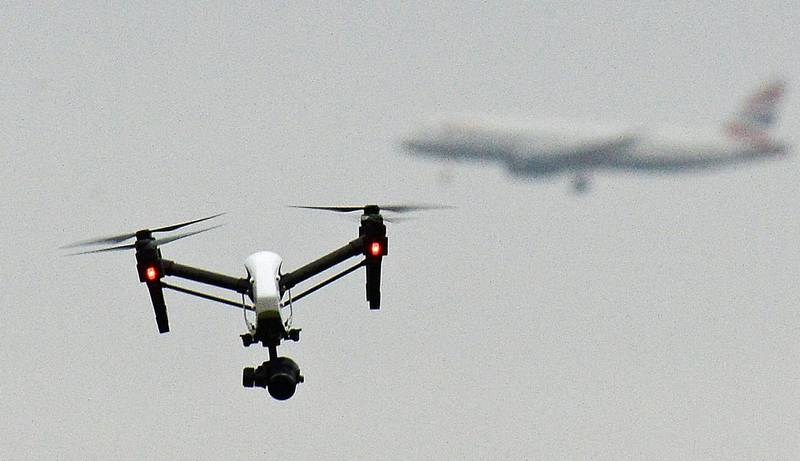 FILE - In this Feb. 25, 2017 file photo, a drone flies in Hanworth Park in west London, as a British Airways 747 plane in the background prepares to land at Heathrow Airport. British officials announced plans Saturday, July 22, 2017 to further regulate drone use in a bid to prevent accidents and threats to commercial aviation. (John Stillwell/PA via AP, File)