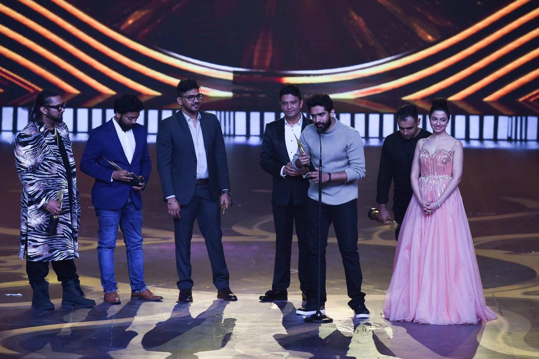 (L-R) Bollywood music directors Honey Singh, Saurabh, Vaibhav, Bhushan Kumar, Amaal Mallik, Rochak Kohli and Divya Khosla Kumar receive the Best Music Direction award for movie 'Sonu Ke Titu Ki Sweety' during the 20th International Indian Film Academy (IIFA) Awards at NSCI Dome in Mumbai on September 18, 2019. / AFP / INDRANIL MUKHERJEE