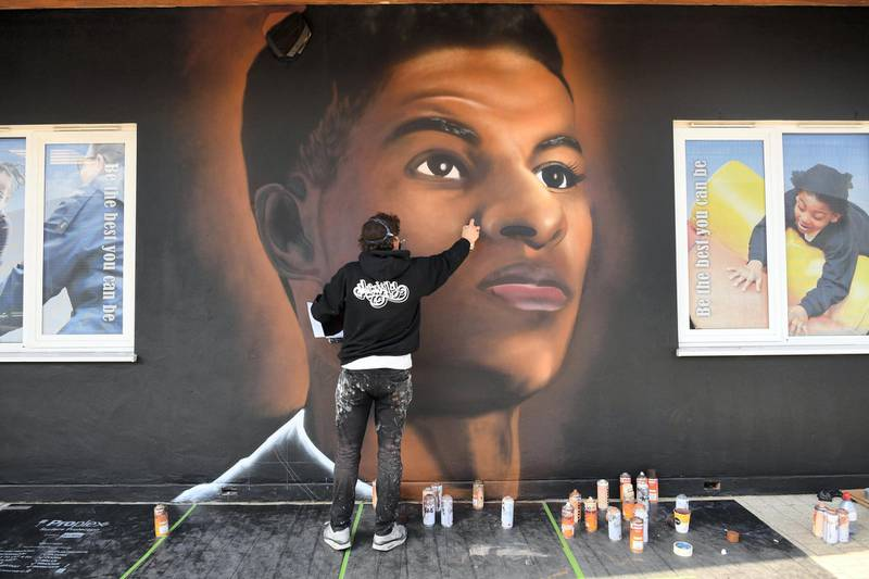 Josh from street artists MurWalls paints a mural of footballer Marcus Rashford on the wall of Gainsborough Primary School in East Ham, east London. Based on an original photograph by Paul Cooper and sponsored by JDS Recruitment, the concept was developed by the students after the huge benefits received for them and their families by Rashford's Free School meals campaign. Picture date: Monday June 7, 2021. (Photo by Stefan Rousseau/PA Images via Getty Images)