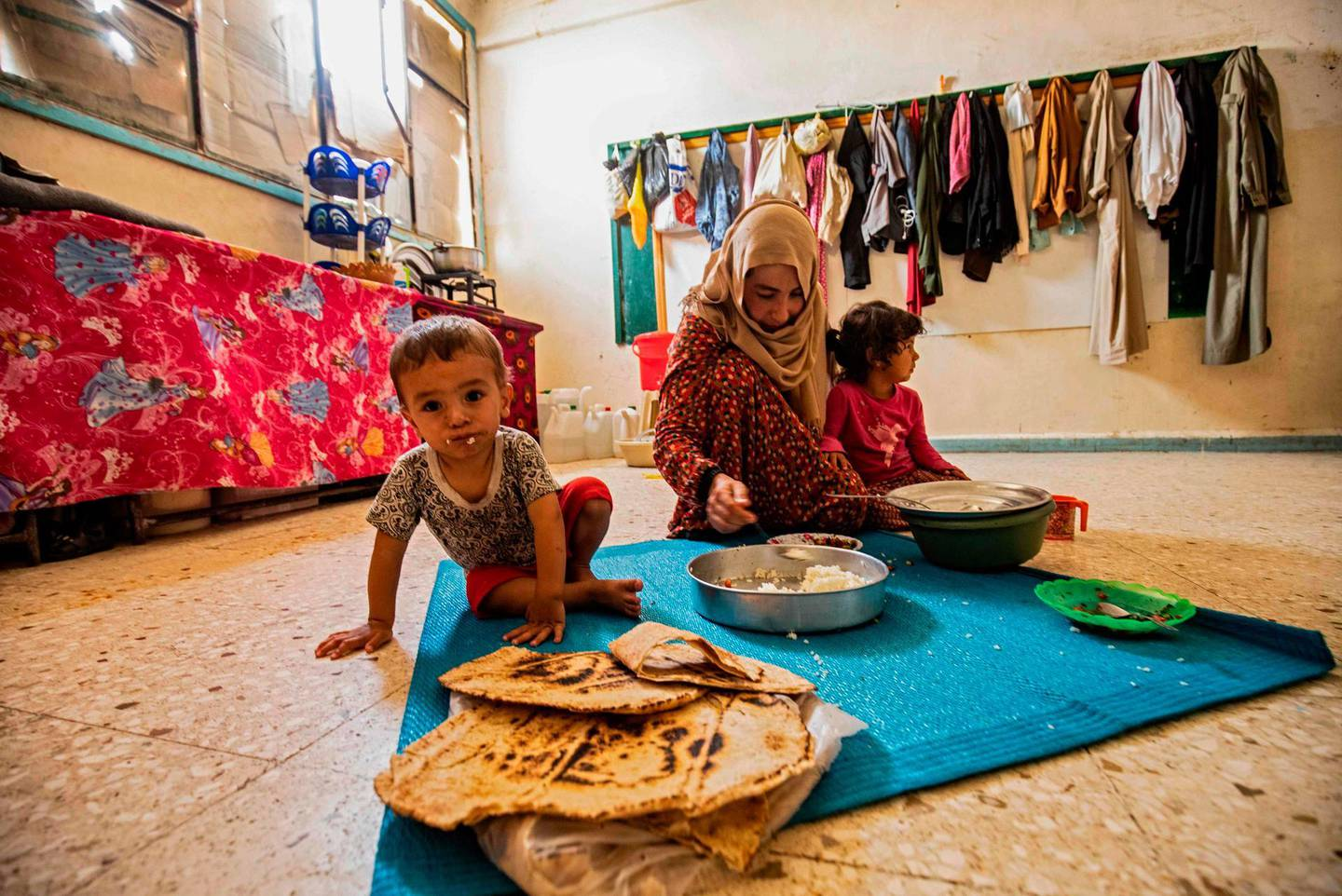 A woman feeds a child while sitting on the floor at a former classroom in a school building where Syrians -- displaced from the area of Ras al-Ain by the Turkish offensive on the northeast -- are staying in the city of Hasakah, on June 30, 2020.  / AFP / Delil SOULEIMAN
