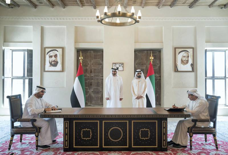 DUBAI, UNITED ARAB EMIRATES - March 20, 2018: HH Sheikh Mohamed bin Zayed Al Nahyan Crown Prince of Abu Dhabi Deputy Supreme Commander of the UAE Armed Forces (back L) and HH Sheikh Mohamed bin Rashid Al Maktoum, Vice-President, Prime Minister of the  UAE, Ruler of Dubai and Minister of Defence (back R), witness the signing of a joint venture agreement between Aldar and Emaar. Seen signing are HE Mohamed Khalifa Al Mubarak, Chairman of the Department of Culture and Tourism and Abu Dhabi Executive Council Member (L) and HE Mohamed Al Abbar, Founder and Chairman of Emaar Properties and Board Member of Eagle Hills (R), in Shindagha Heritage District.   ( Mohamed Al Hammadi / Crown Prince Court - Abu Dhabi ) ---
