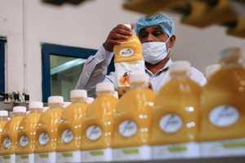FUJAIRAH - APRIL 7,2009 - A worker double check the Masafi juice  before  it pass on the at Masafi Plant in Fujairah.( Paulo Vecina/The National ) *** Local Caption ***  PV Masafi 30.JPG