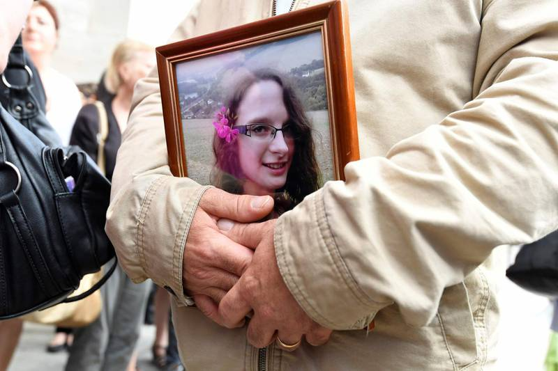 (FILES) In this file photo taken on June 06, 2018, a man holds a picture of murdered French au-pair Sophie Lionnet following her funeral in Sens.  A French couple living in London who murdered their au-pair and tried to dispose of the body by burning it in their back garden were sentenced to life in prison, on June 26, 2018, with a minimum of 30 years. The Old Bailey court in London sentenced Sabrina Kouider, who is undergoing psychiatric treatment, and Ouissem Medouni for the September 2017 killing of 21-year-old Sophie Lionnet. / AFP / Bertrand GUAY