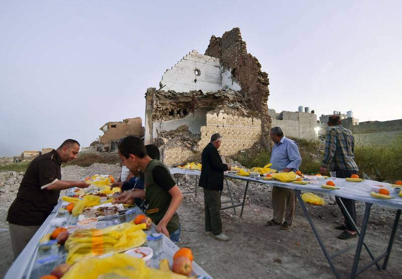 TOPSHOT - Iraqis share a collective iftar, the evening meal that will end the daily fast at sunset, on the second day of the Islamic holy month of Ramadan, in the war-ravaged old part of the northern city of Mosul, on April 15, 2021.   / AFP / Zaid AL-OBEIDI