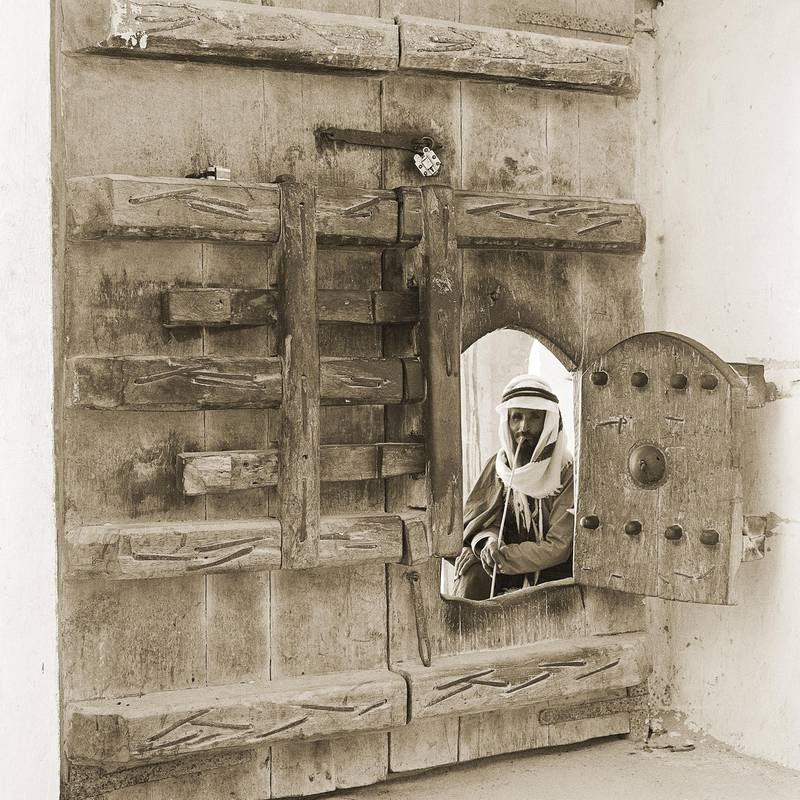 guard looking through an opening in the gate of Al Hosn, 1960.  Courtesy National Center for Documentation and Research.