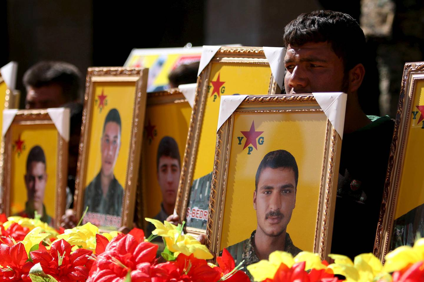 FILE PHOTO: Relatives carry pictures of fighters from the Kurdish People's Protection Units (YPG), who were killed when Islamic State militants attacked the town of Tel Abyad on the Turkish border at the weekend, during their funeral procession at Ras al-Ain city, in Hasakah province,  Syria March 2, 2016. REUTERS/Rodi Said/File Photo