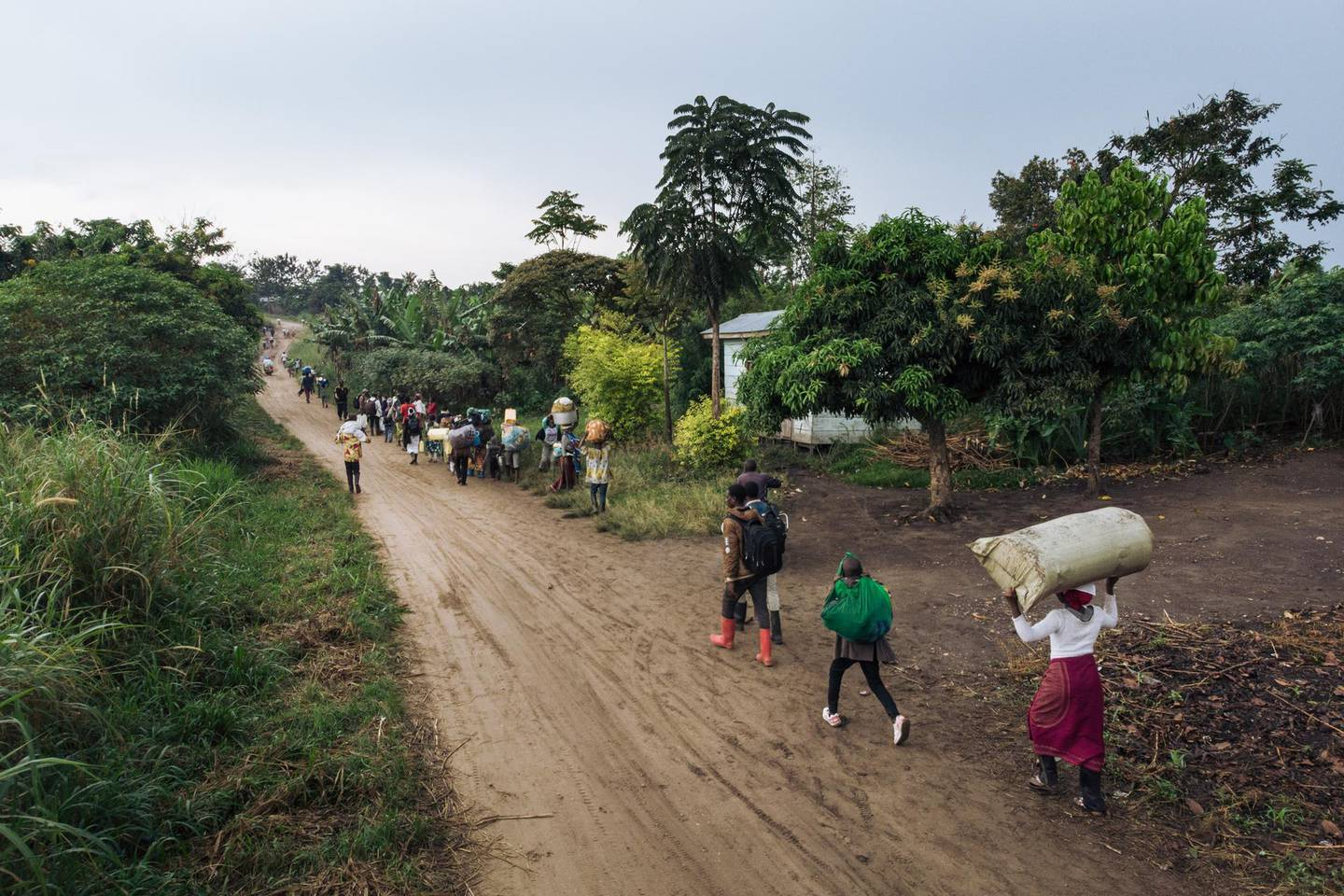 Displaced people carrying their belongings flee the scene of an attack allegedly perpetrated by the rebel group Allied Democratic Forces (ADF) in the Halungupa village near Beni on February 18, 2020. (Photo by Alexis Huguet / AFP)