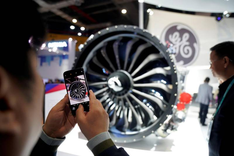 FILE PHOTO: A man takes a picture of a General Electric (GE) engine during the China International Import Expo (CIIE), at the National Exhibition and Convention Center in Shanghai, China November 6, 2018. REUTERS/Aly Song/File Photo