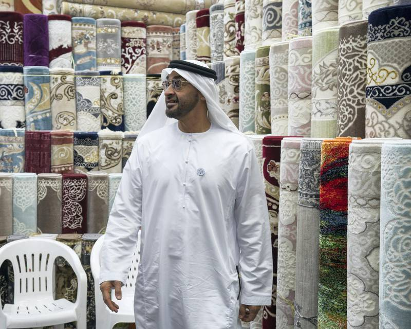 ABU DHABI, UNITED ARAB EMIRATES -  February 22, 2018: HH Sheikh Mohamed bin Zayed Al Nahyan, Crown Prince of Abu Dhabi and Deputy Supreme Commander of the UAE Armed Forces (C), visits the carpet market in the Mina Zayed Port area.  ( Ryan Carter for the Crown Prince Court - Abu Dhabi ) ---