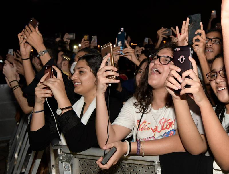 In this Thursday, July 18, 2019, photo, fans film and wave during the concert of Jeddah World Fest, at the King Abdullah Sports Stadium, in Jeddah, Saudi Arabia. Janet Jackson, Chris Brown, 50 Cent, Future and Tyga have been added to the lineup for the concert in Saudi Arabia that Nicki Minaj pulled out of because of human rights concerns. (AP Photo/Khalid Alhaj)