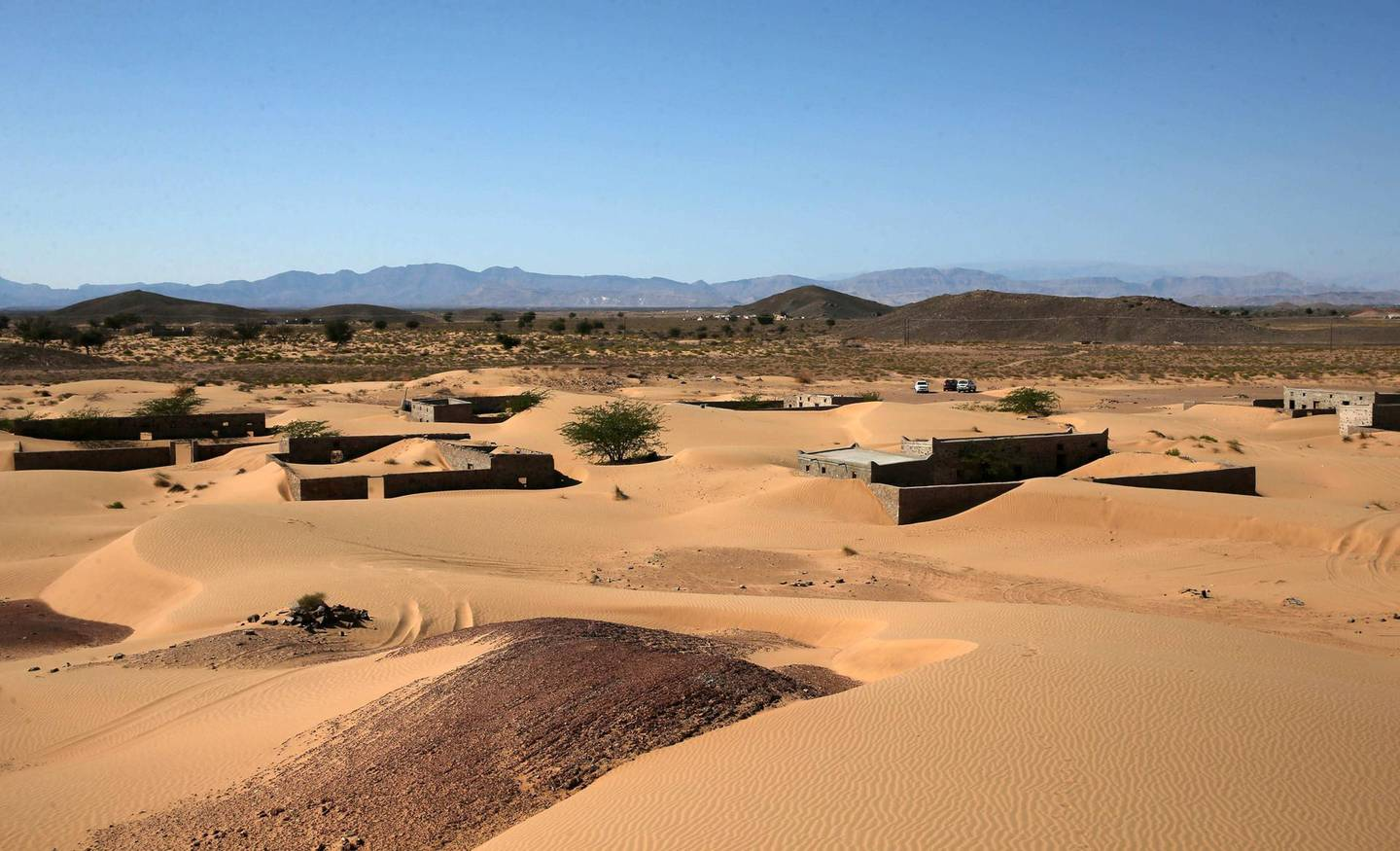 This picture taken on December 31, 2020, shows abandoned houses in the Omani village of Wadi al-Murr, about 400 kms (250 miles) southwest of the capital Muscat. Encroaching desert sands have left little evidence that Wadi al-Murr ever existed, but former inhabitants, while resigned to its destruction, are trying to preserve its memory. The advance of the desert is not specific to the sultanate of Oman, and experts say climate change is one of the factors propelling the phenomenon in different parts of the world.  / AFP / MOHAMMED MAHJOUB