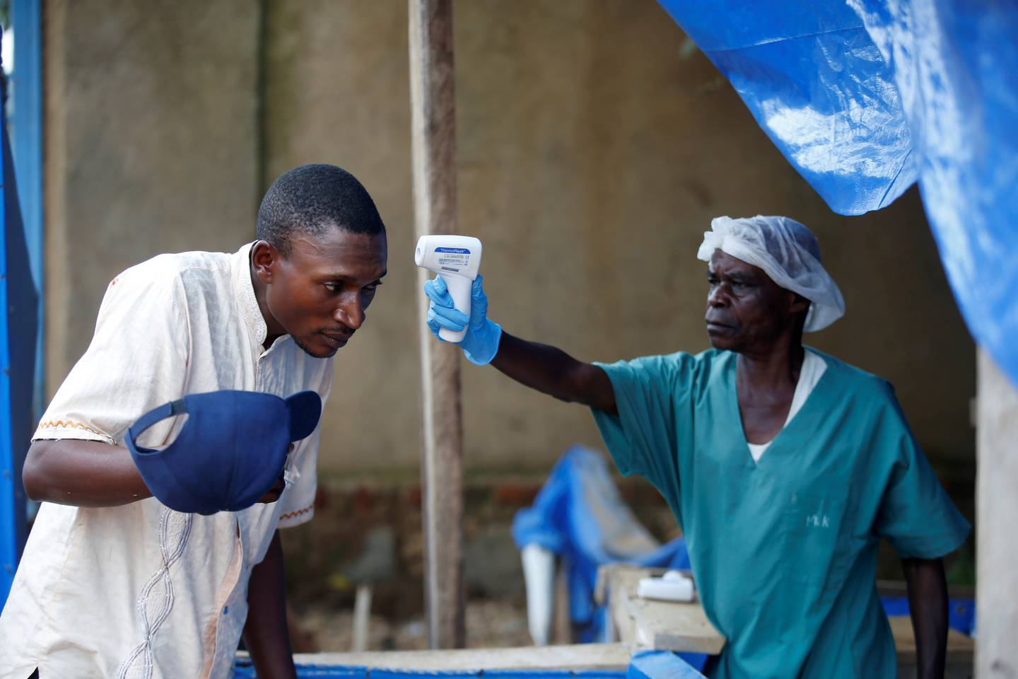 FILE PHOTO: A health worker measures the temperature of a man entering the ALIMA (The Alliance for International Medical Action) Ebola treatment centre in Beni, in the Democratic Republic of Congo, April 1, 2019. Picture taken April 1, 2019. REUTERS/Baz Ratner/File Photo