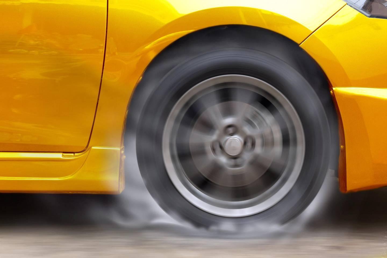 Gold car racing spinning wheel burns rubber on floor.