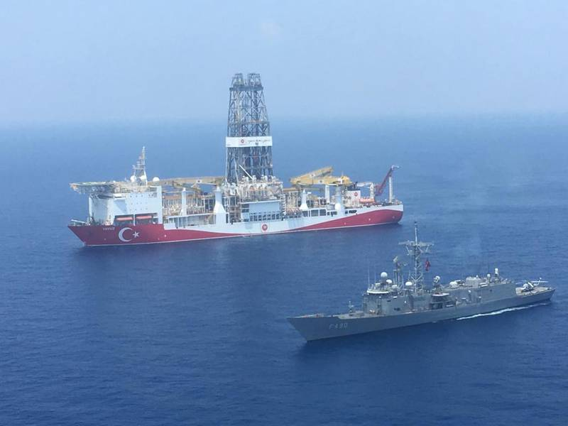 """A handout photograph taken and relased by the Turkish Defence Ministery on July 9,2019 shows a Turkish Navy warship patroling next to Turkey's drilling ship """"Fatih"""" dispatched towards the eastern Mediterranean near Cyprus. - Turkey will """"increase"""" its activities off Cyprus after the EU approved measures to punish Ankara for drilling operations in the eastern Mediterranean, the Turkish foreign minister said on July 16, 2019. (Photo by DEFENCE MINISTERY PRESS SERVICE / TURKISH DEFENCE MINISTRY / AFP) / RESTRICTED TO EDITORIAL USE - MANDATORY CREDIT """"AFP PHOTO / TURKISH DEFENCE MINISTRY"""" - NO MARKETING - NO ADVERTISING CAMPAIGNS - DISTRIBUTED AS A SERVICE TO CLIENTS"""