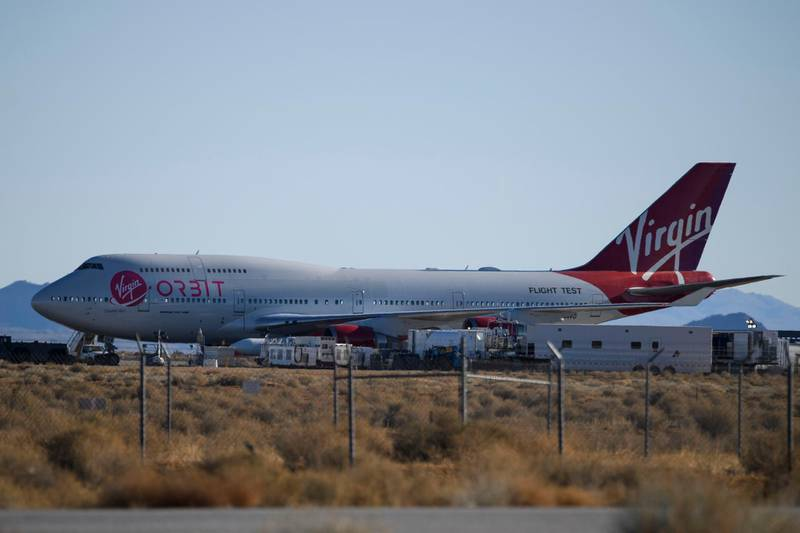 """The Virgin Orbit """"Cosmic Girl"""" - a modified Boeing Co. 747-400 carrying a LauncherOne rocket under it's wing - is prepared on the tarmac for the Launch Demo 2 mission from Mojave Air and Space Port on January 17, 2021 in Mojave, California. - The LauncherOne rocket, which will release from the wing of the Boeing 747 before ignition, contains small research satellites, known as CubeSats for NASA's Educational Launch of Nanosatellites (ELaNa) 20 mission developed by nine research universities and a NASA center. (Photo by Patrick T. FALLON / AFP)"""