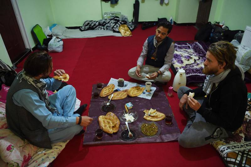 In this photo taken on November 11, 2018, Afghan Couchsurfing host Naser Majidi (C), 27, eats brekfast with his guests Norwegian tourist Jorn Bjorn Augestad (R), 29, and Dutch tourist Ciaran Barr, 24, at a house in Kabul.  Once a popular stop on the well-worn hippy trail between Europe and South Asia in the 1970s, Afghanistan has seen the number of foreign travellers crossing its borders dwindle in the past four decades of almost non-stop conflict. But dozens still make the dangerous journey every year, ignoring clear warnings from their own governments to stay away from a country infested with suicide attackers, kidnappers and armed robbers, and which by some estimates is now the world's deadliest conflict zone.  - TO GO WITH AFP STORY AFGHANISTAN-LEISURE,FEATURE BY ALLISON JACKSON  / AFP / WAKIL KOHSAR / TO GO WITH AFP STORY AFGHANISTAN-LEISURE,FEATURE BY ALLISON JACKSON
