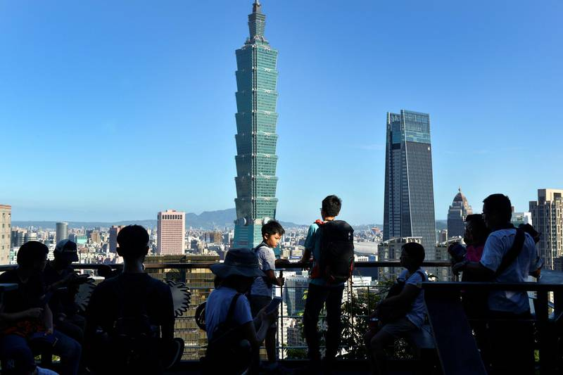 People gather on a viewing deck at Elephant Mountain before Taipei 101 Tower (C) and Nan Shan Tower (centre R) in Taipei on July 14, 2018. (Photo by Chris STOWERS / AFP)