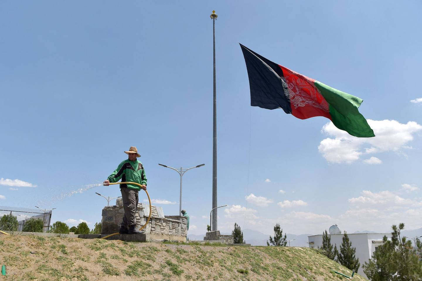 A worker waters a lawn near an Afghan national flag flying at half-mast in Kabul on May 11, 2021 during a national day of mourning announced by Afghan President Ashraf Ghani to condemn the recent terrorist attacks. / AFP / WAKIL KOHSAR