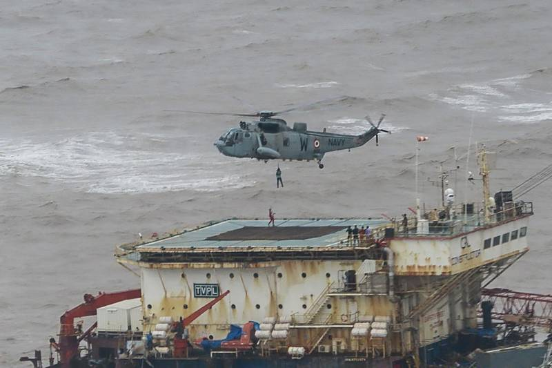 This handout photograph taken on May 18, 2021 and released by the Indian Navy shows stranded workers from a barge, which had gone adrift amidst heavy rain and strong winds due to Cyclone Tauktae, being airlifted by naval personnel on an Indian Navy Seaking helicopterduring an evacuation operation, in the Arabian sea. At least 27 people were dead and more than 90 missing on May 18 after a monster cyclone slammed India, compounding the country's woes as it recorded a new record number of coronavirus deaths in 24 hours. / AFP / INDIAN NAVY / -