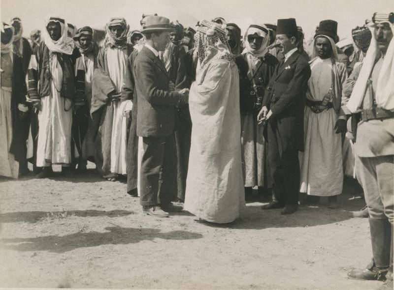 T. E. Lawrence, shaking hands with Amir Abdullah, with other men gathered around behind them. Meetings of British, Arab, and Bedouin officials in Amman, Jordan, April. Courtesy Library of Congress, Prints & Photographs Division