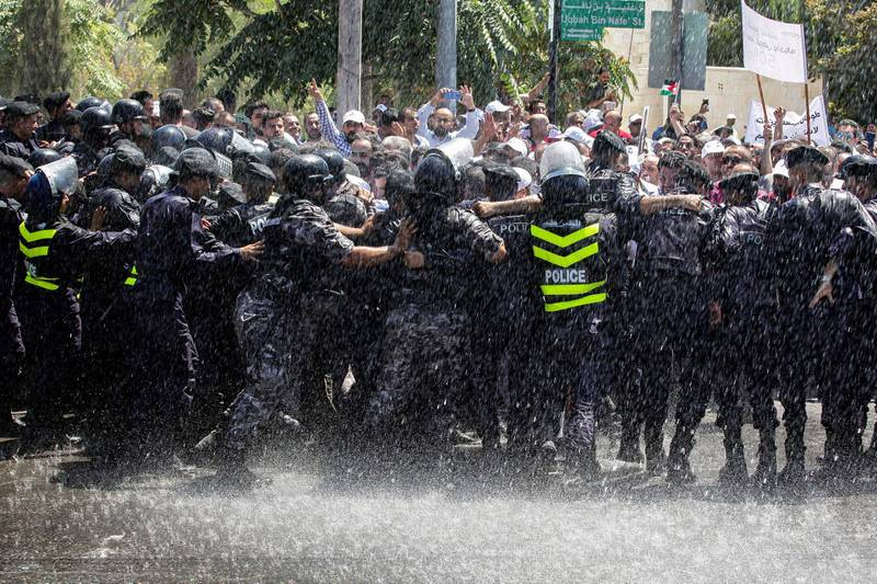 TOPSHOT - Jordanian teachers clash with security forces during a protest in the capital Amman on September 5, 2019. Thousands of public school teachers marched in central Amman demanding higher wages, just four days after the start of school year, as the Jordan Teachers Association's (JTA) demanded a 50 percent salary increase according to its leader. / AFP / Khalil MAZRAAWI