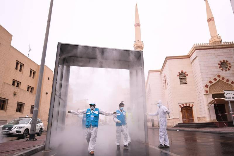 Health volunteers pass through a sterilisation chamber installed to disinfect residents entering and leaving the Naif area in the Gulf emirate of Dubai during the COVID-19 coronavirus outbreak, on April 15, 2020.  / AFP / KARIM SAHIB