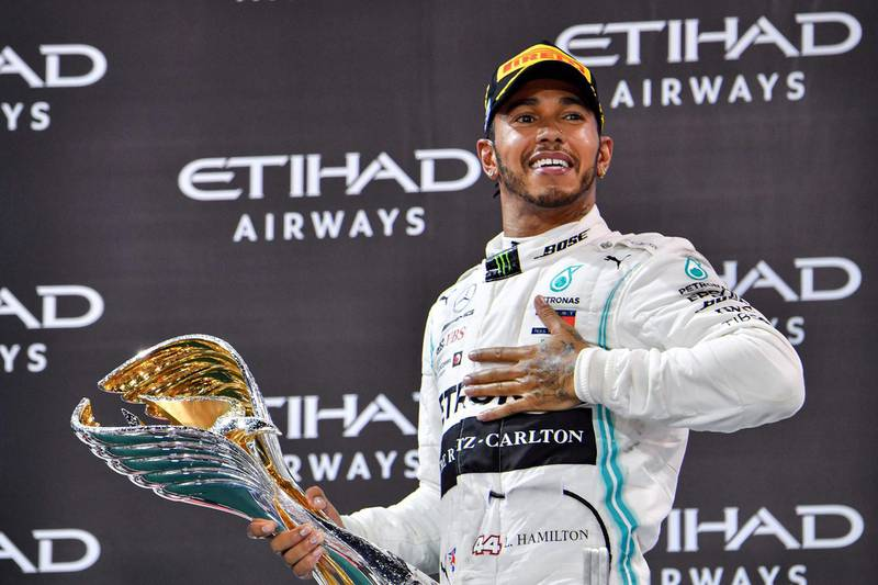 (FILES) In this file photo taken on December 1, 2019 Mercedes' British driver Lewis Hamilton celebrates his win at the Yas Marina Circuit in Abu Dhabi, after the final race of the Formula One Grand Prix season. Lewis Hamilton will launch his bid to equal Michael Schumacher's total of seven world championships and break a clutch of other F1 records when the Australian Grand Prix opens the 2020 season on March 15, 2020. / AFP / GIUSEPPE CACACE