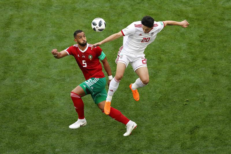SAINT PETERSBURG, RUSSIA - JUNE 15:  Sardar Azmoun of Iran wins a header from Mehdi Benatia of Morocco during the 2018 FIFA World Cup Russia group B match between Morocco and Iran at Saint Petersburg Stadium on June 15, 2018 in Saint Petersburg, Russia.  (Photo by Francois Nel/Getty Images)