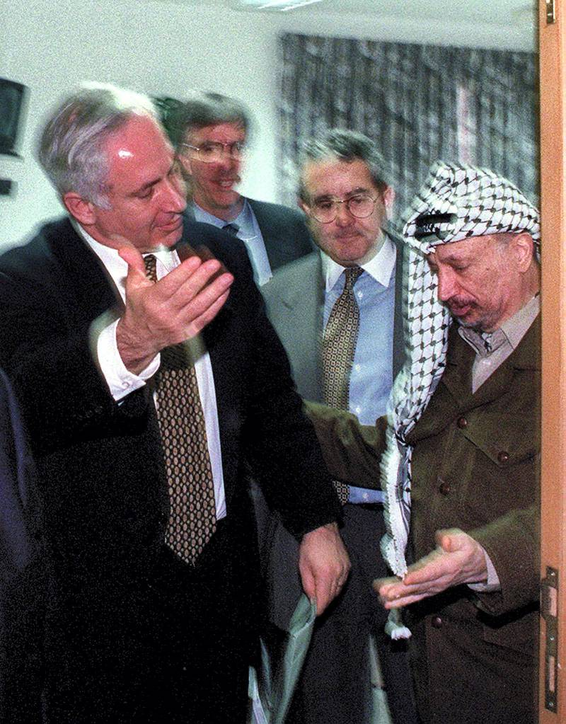 """Palestinian President Yasser Arafat (R) and Israeli Prime Minister Benjamin Netanyahu both gesture for the other to leave a meeting December 24 in the Israeli Civil Administration headquarters located along the Israeli - Gaza Strip border area. The two leaders met for for over three hours in a bid to clinch the agreement on the long-delayed Israeli troop redeployment in Hebron. Although no agreement was reached U.S. envoy Dennis-Ross said that """"real progress"""" was made towards the long-elusive accord."""