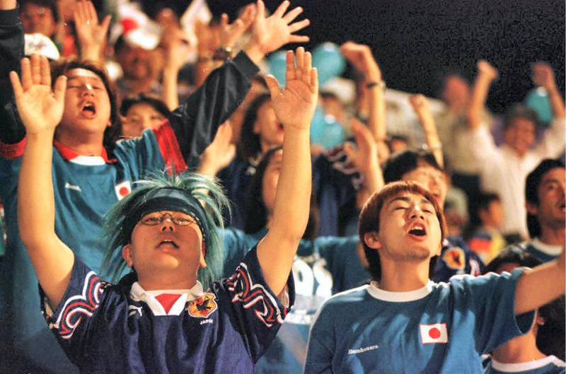 Japanese suporters celebrate the victory of their team against Uzbekistan, during their Asian cup in Al Ain staduim 09 December. Japan defeated Uzbekistan 4-0. (Photo by JORGE FERRARI / AFP)