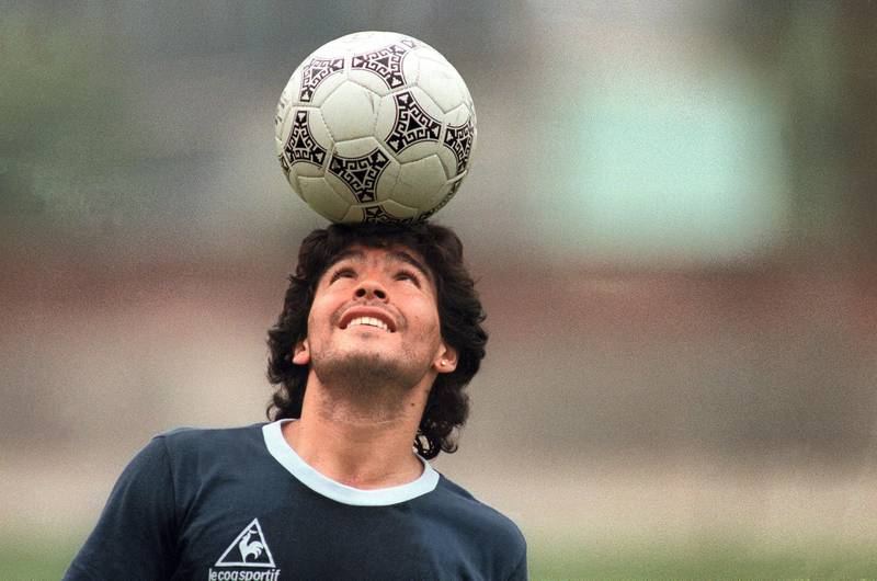 (FILES) In this file picture taken on May 22, 1986 Argentine football star Diego Maradona, wearing a diamond earring, balances a soccer ball on his head as he walks off the practice field following the national team's practice session in Mexico City. Argentine football legend Diego Maradona turns 60 on October 30, 2020.   / AFP / JORGE DURAN