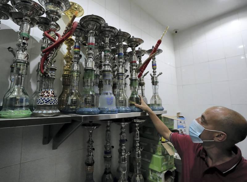 Ras Al Khaimah, United Arab Emirates - Reporter: Tito Al Ghanaima prepares shisha at Orkied Cafe. Shisha cafes are now opening in RAK. Thursday, August 6th, 2020. Ras Al Khaimah. Chris Whiteoak / The National