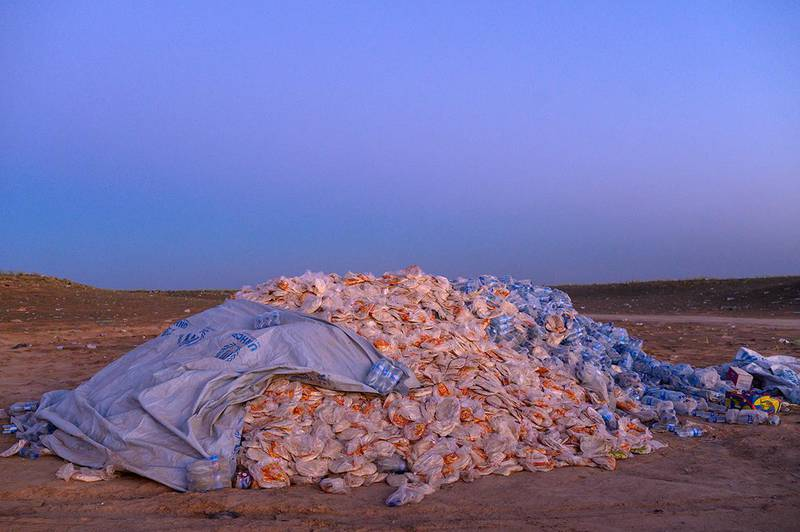 This picture taken on March 9, 2019 shows a pile of food aid composed of bread and water bottles in the desert, left for new coming civilians out of the town of Baghouz, in the eastern Syrian province of Deir Ezzor. - More than 7000 people, mostly women and children, have fled the shrinking pocket over the past days, as US-backed forces press ahead with an offensive to crush holdout jihadists. (Photo by BULENT KILIC / AFP)