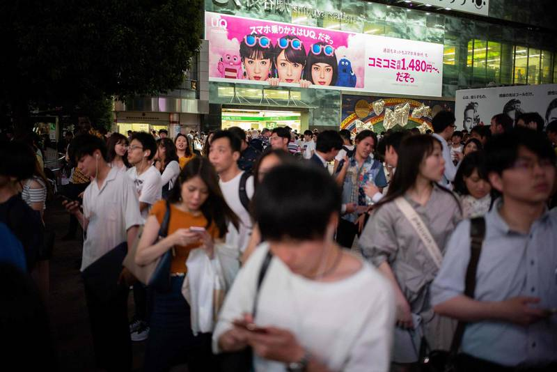 This photo taken on June 30, 2018 shows people looking at their phones in Shibuya in Tokyo. / AFP / Martin BUREAU