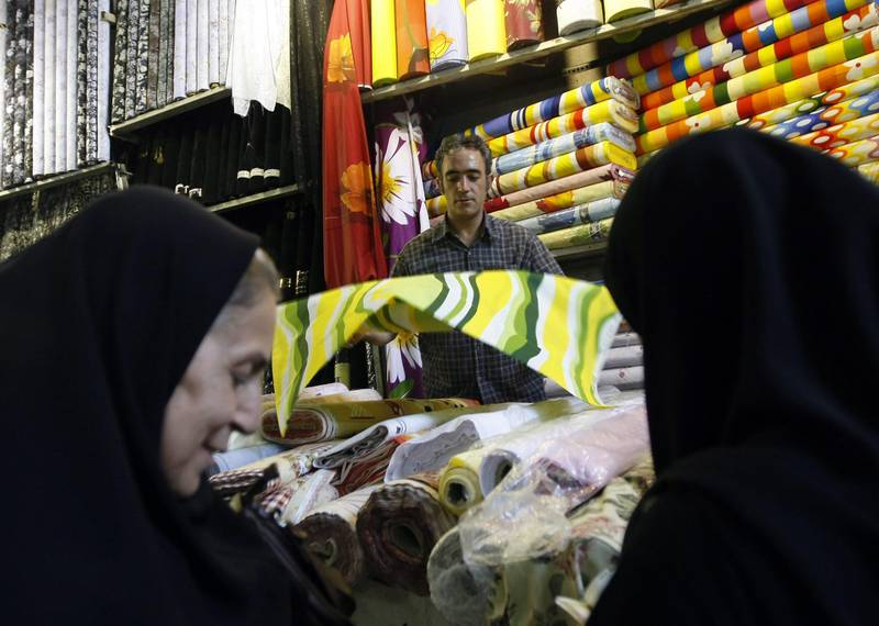 Iranian women buy textile at a shop in Tehran's Bazaar on October 8, 2008. Iran's inflation topped 29 percent in the calendar month of Shahrivar that ended September 21, continuing an upward trend of the past few months, a central bank report said today. AFP PHOTO/BEHROUZ MEHRI *** Local Caption ***  437206-01-08.jpg