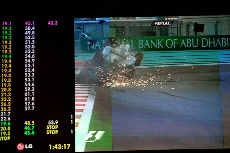 A picture of a giant screen shows Mercedes' German driver Nico Rosberg (UP) crashing into HRT F1 Team's Indian driver Narain Karthikeyan at the Yas Marina circuit in Abu Dhabi during the Abu Dhabi Formula One Grand Prix on November 4, 2012. AFP PHOTO/TOM GANDOLFINI (Photo by Tom Gandolfini / AFP)