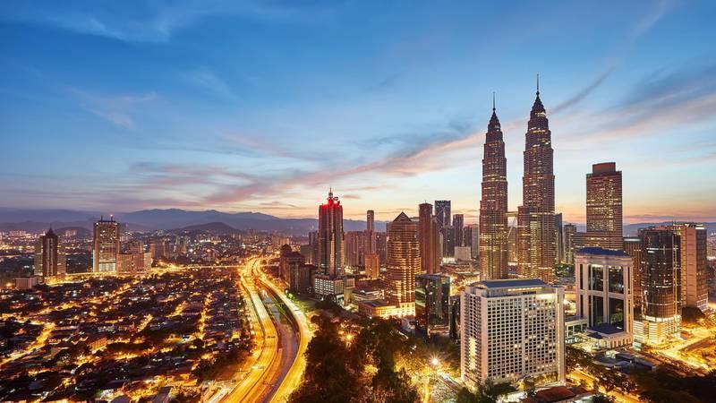 A 16x9 view of beautiful sunrise overlooking national landmark of Malaysia, The Petronas Twin Towers.