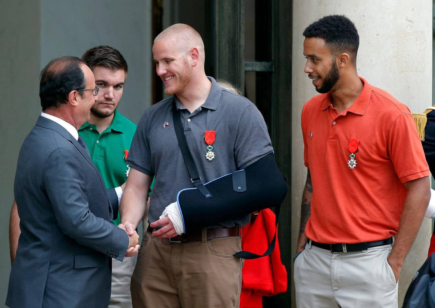 FILE - In this Aug. 24, 2015 file photo, French President Francois Hollande bids farewell to U.S. Airman Spencer Stone as U.S. National Guardsman Alek Skarlatos of Roseburg, Ore., second from left, and Anthony Sadler, a senior at Sacramento State University in California, right, after Hollande awarded them the French Legion of Honor at the Elysee Palace in Paris. The three Sacramento-area men are lorded for their bravery in thwarting a terror attack on a French train in 2015. Islamic State operative Ayoub El Khazzani goes on trial in France Monday Nov. 16, 2020, on terror charges for appearing on a train with an arsenal of weapons and shooting one passenger in 2015. (AP Photo/Michel Euler, File)