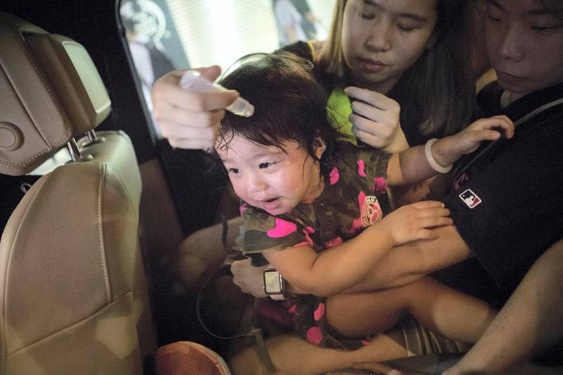 HONG KONG. SCHOOL BUS FEATURE: A young girl is treated by a medic in the back of Chen's car after being effected by tear gas during protests in the Mong Kok area of Hong Kong. 'School Buses', are the collective name to a group of volunteers, including Chen, who offer free transport for people who need help getting away from the protests safely.