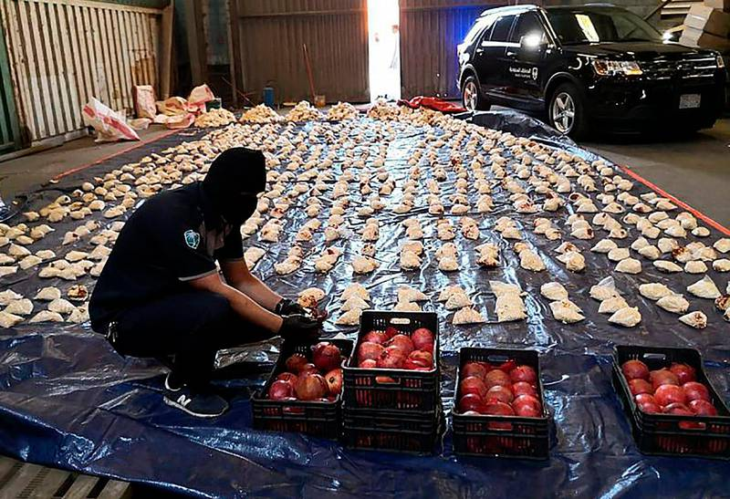 In this photo released by Saudi Press Agency, a Saudi custom officer opens imported pomegranates, as customs foiled a attempt to smuggle millions of Captagon pills, which they said where coming from Lebanon, at Jiddah Islamic Port, Saudi Arabia, Friday, April 23, 2021. Saudi Arabia will ban Lebanese fruits and vegetables entering the kingdom or passing through it because those shipments have been increasingly used to smuggle drugs, the official news agency reported Friday. (Saudi Press Agency via AP)