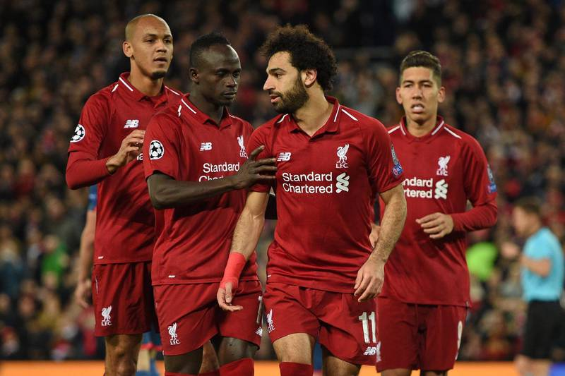 Liverpool's Egyptian midfielder Mohamed Salah (2nd R) celebrates with Liverpool's Senegalese striker Sadio Mane (2nd L) and Liverpool's Brazilian midfielder Fabinho (L) after scoring their third goal from the penalty spot during the UEFA Champions League group C football match between Liverpool and Red Star Belgrade at Anfield in Liverpool, north west England on October 24, 2018.  / AFP / Oli SCARFF