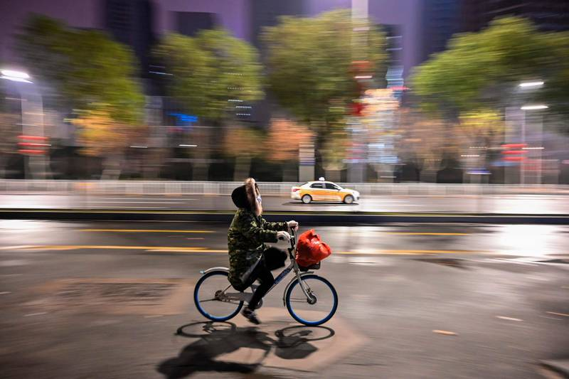 A person wearing a protective facemask rides a bicycle along a street in Wuhan on January 26, 2020, a city at the epicentre of a viral outbreak that has killed at least 56 people and infected nearly 2,000. China on January 26 expanded drastic travel restrictions to contain an epidemic that has killed 56 people and infected nearly 2,000, as the United States, France and Japan prepared to evacuate their citizens from a quarantined city at the outbreak's epicentre. / AFP / Hector RETAMAL