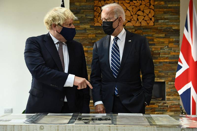 Britain's Prime Minister Boris Johnson (L) and US President Joe Biden, both wearing face coverings due to Covid-19, view a display ahead of their a bi-lateral meeting at Carbis Bay, Cornwall on June 10, 2021, ahead of the three-day G7 summit being held from 11-13 June.  G7 leaders from Canada, France, Germany, Italy, Japan, the UK and the United States meet this weekend for the first time in nearly two years, for the three-day talks in Carbis Bay, Cornwall. -   / AFP / Brendan Smialowski
